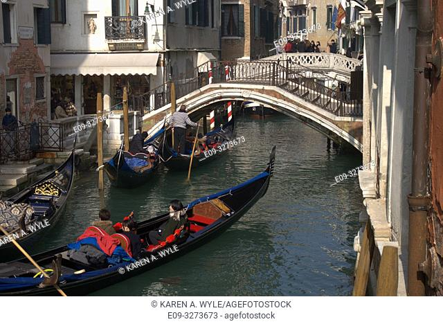 canal with three gondolas and two bridges, Venice, Italy