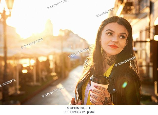 Young woman outdoors, holding coffee cup, tattoos on hands and neck