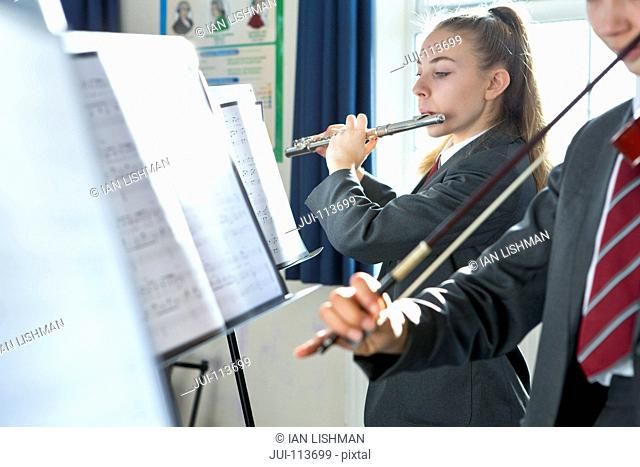 High school students playing flute and violin at music stand in music class