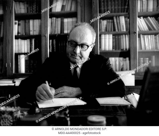 Giuseppe Saragat sitting at the desk and writing. Italian deputy and Secretary of Italian Democratic Socialist Party (PSDI) Giuseppe Saragat sitting at the desk...
