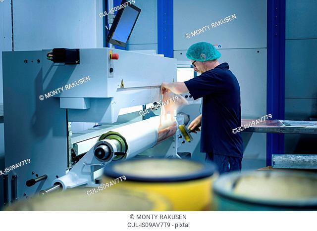 Worker preparing printing plates in food packaging printing factory