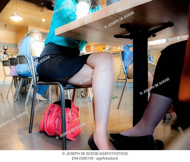 Partial view of the legs of 2 women under a table in a restaurant