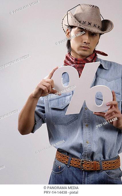 Close-up of a young man holding dollar sign
