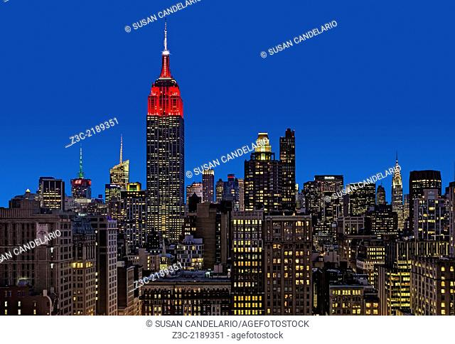 An upper view during the blue hour to the Empire State Building ESB along other high rises in the Flatiron District. The Empire State Building is illuminated in...