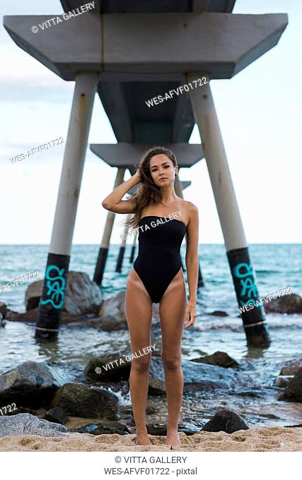 Portrait of beautiful young woman wearing swimsuit standing at the seafront