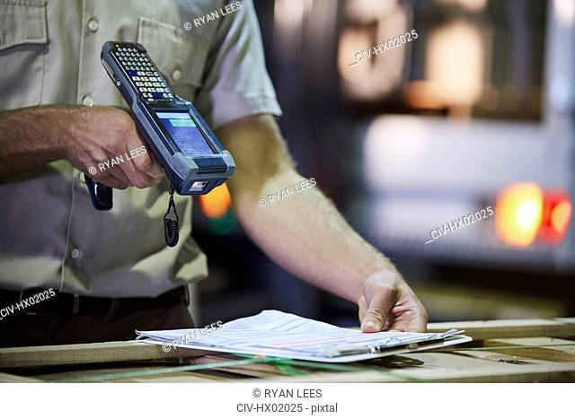 Worker with scanner scanning paperwork in distribution warehouse