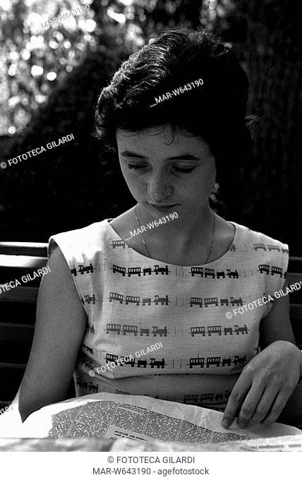 LETTURA Ritratto fotografico di giovane ragazza mentre legge un quotidiano. Ha i capelli corti e indossa una camicetta senza maniche chiara decorata con trenini