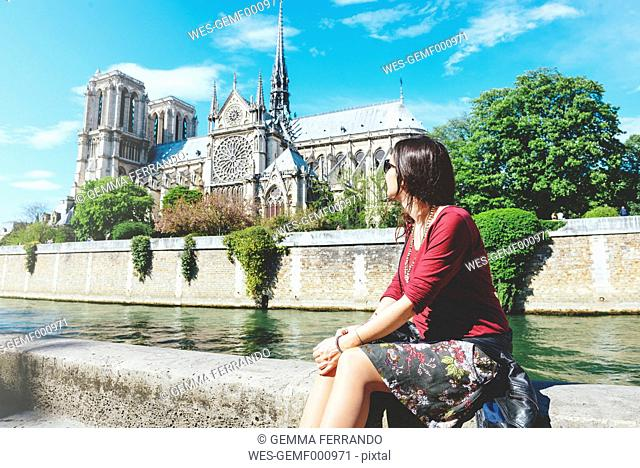 France, Paris, woman sitting on the bank of the Seine river in front of Notre-Dame de Paris