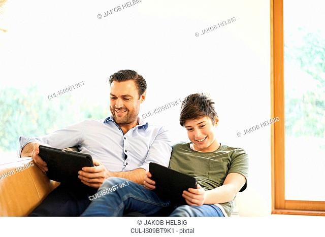 Boy and father looking at digital tablets whilst reclining on sofa