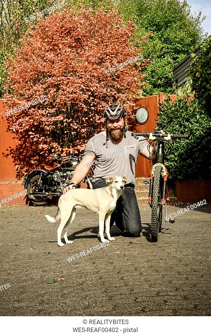 Portrait of smiling man with dog and bicycle