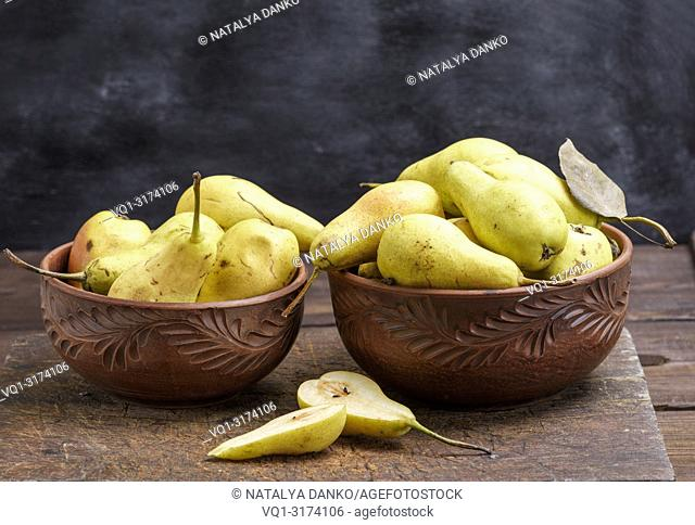 ripe fresh yellow pears in a clay bowl on a brown wooden table, black background