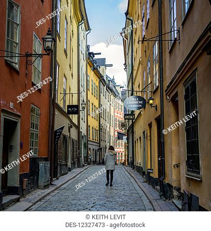 A Woman Walking Down A Street Between Colourful Retail And Residential Buildings; Stockholm, Sweden