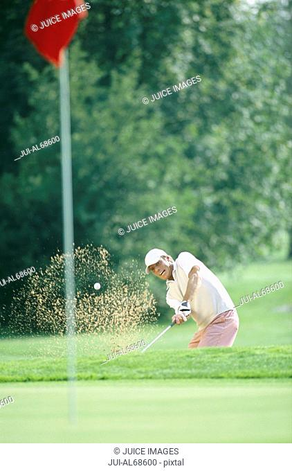 View of a man hitting a golf ball out of a bunker and onto the green on a golf course