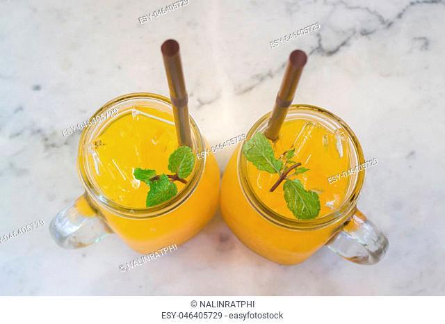 Orange juice with ice cube on marble table, stock photo