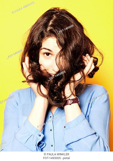 Portrait of young woman covering face with hair against yellow background