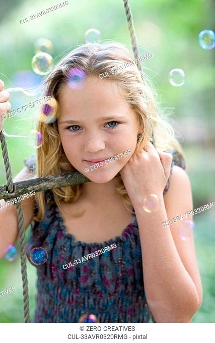Girl climbing rope ladder with bubbles