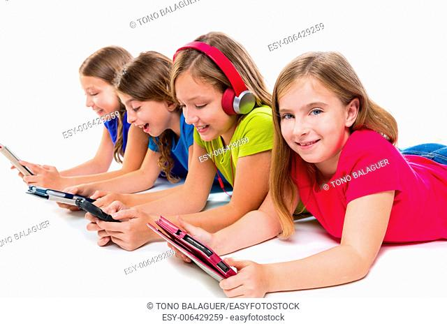 sisters cousins kid girls with tech tablets and smatphones in a row lying on white background