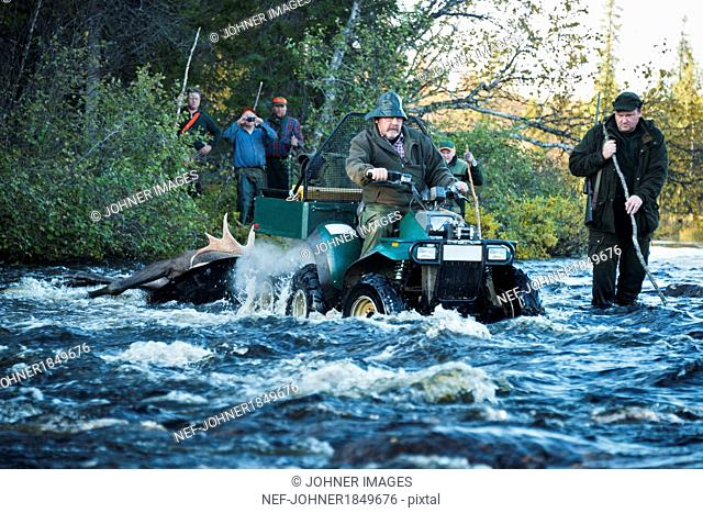 Hunters with prey crossing river