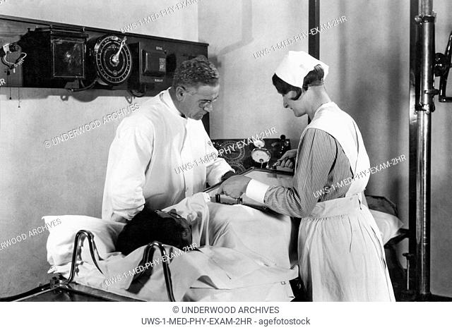 Battle Creek, Michigan: c. 1928.A doctor and nurse performing a fluoroscopic examination of the stomach during the Barium Meal X-Ray Examination at John Harvey...