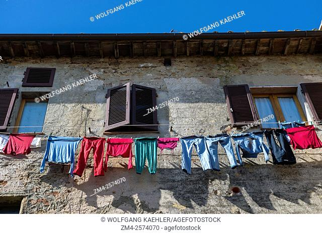 Colorful laundry is hanging outside a house to dry in Pienza, Val d'Orcia, Tuscany, Italy