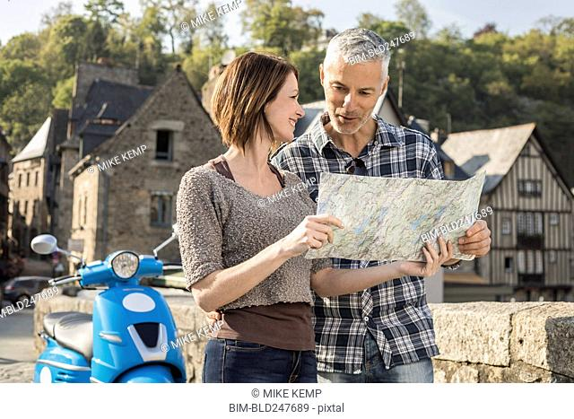 Caucasian couple near blue motor scooter reading map