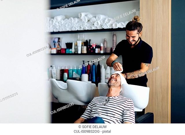 Male hairstylist putting towel on male customer's hair in hair salon