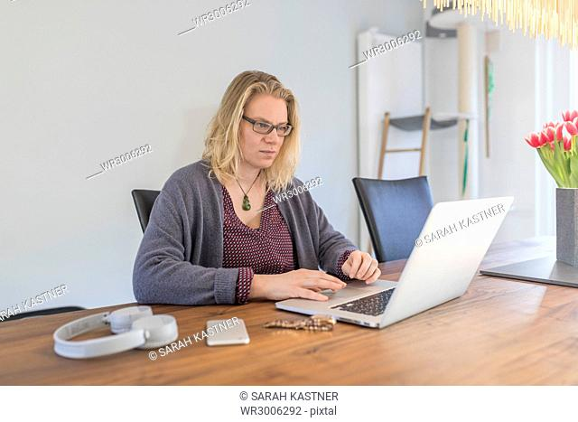 Woman working with laptop at kitchen table