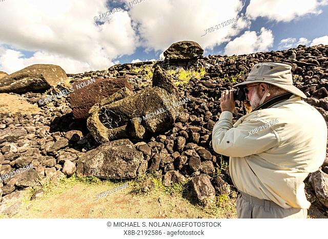 Photographer with fallen moai head and red scoria topknot at Ahu Akahanga on Easter Island (Isla de Pascua, Rapa Nui), Chile