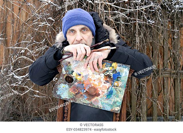 Male painter leaning on a chair while holding paintbrushes and palette, outdoor shot