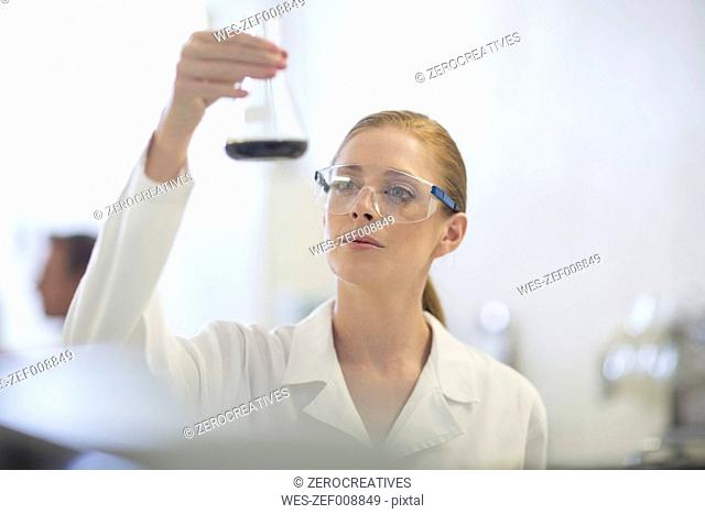 Young woman examining liquid in lab