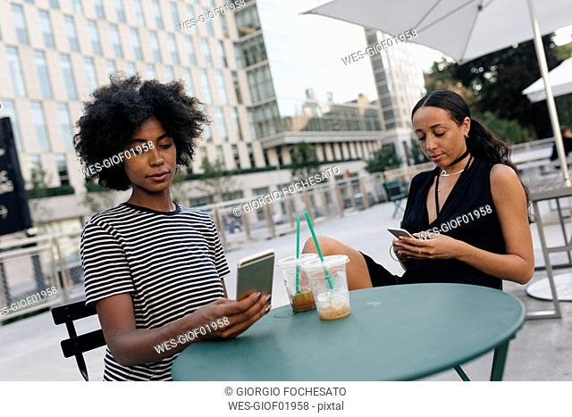 Two friends sitting at pavement cafe looking at their cell phones