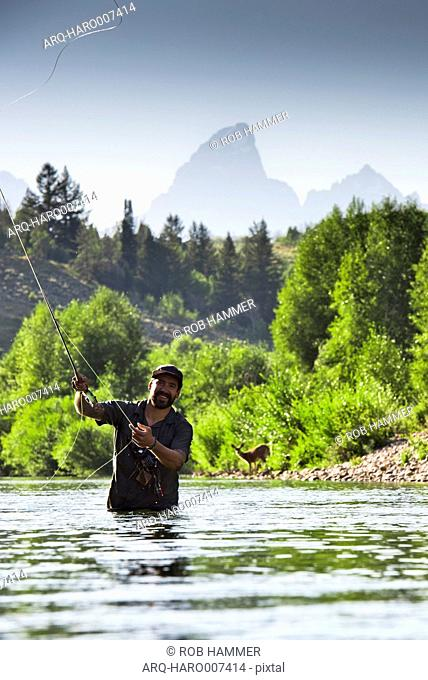 A Fly Fisherman In The Gros Ventre River With Grand Teton Mountains In The Background, Jackson Hole, Wyoming