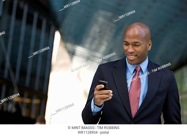 Business people outdoors, keeping in touch while on the go. A man in a suit checking his phone