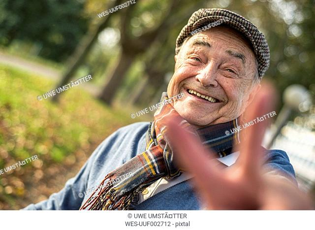 Portrait of happy senior man outdoors doing victory sign