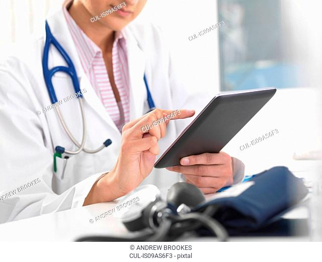 Cropped shot of female doctor using digital tablet touchscreen to update medical records