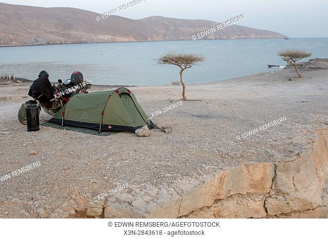 Small campsite and motorbike are set up overlooking the Musandam coast in Khasab, Oman