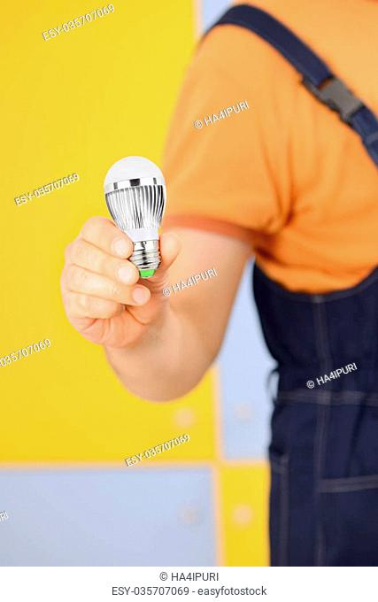 Worker in overall holding modern LED bulb in his hand