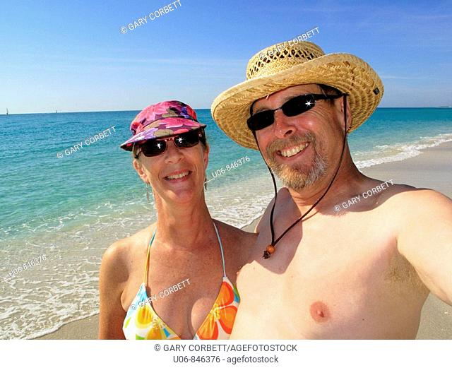 a middle aged couple at the beach in bathing suits
