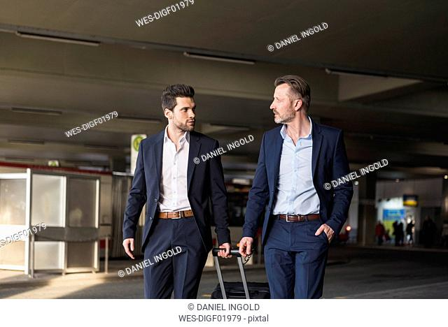 Two businessmen with rolling suitcase at bus terminal