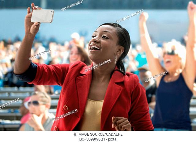 Woman in stadium, recording event with her phone