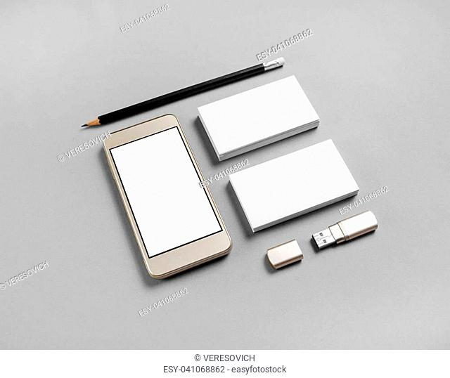 Cellphone and stationery on gray paper background. Blank business cards, pencil, smartphone and usb flash drive