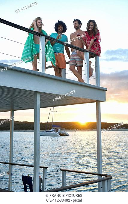 Young friends hanging out and drinking on summer houseboat at sunset