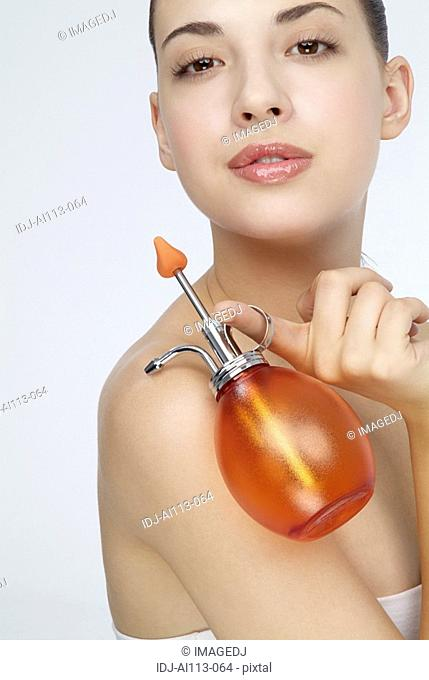 Close-up of a young woman holding perfume bottle
