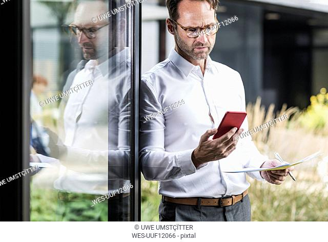 Businessman with paperslooking at cell phone