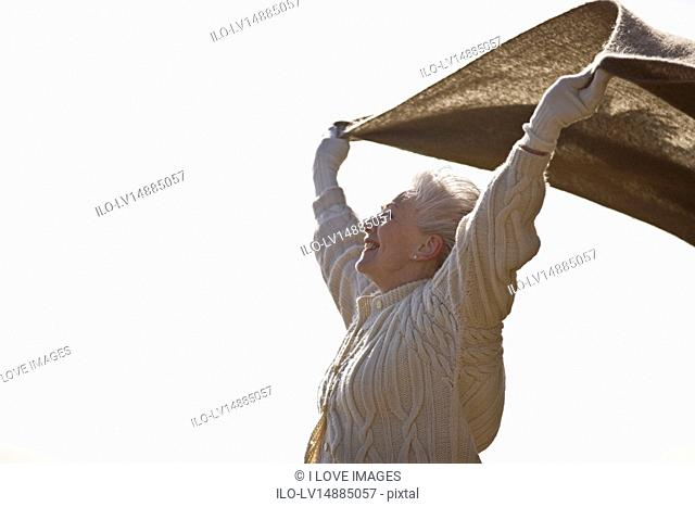 A senior woman holding a blanket into the wind