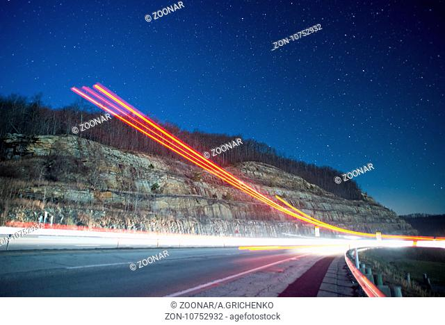 light trails at night in the mountains from outgoing traffic
