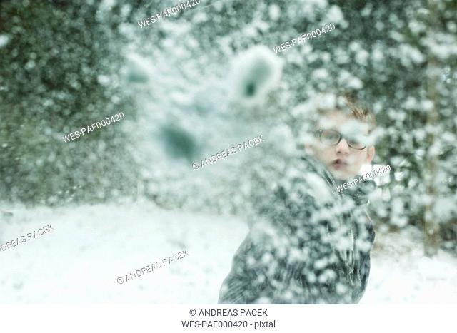 Boy throwing snowball against windscreen