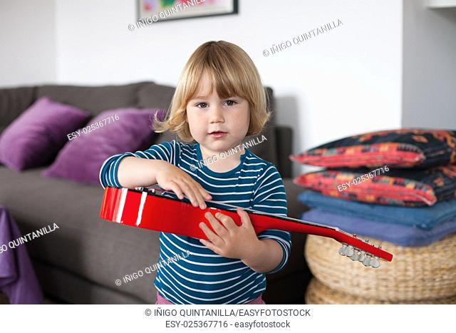 blonde two years old child with striped blue and white sweater inside home playing with hand red spanish little guitar and looking