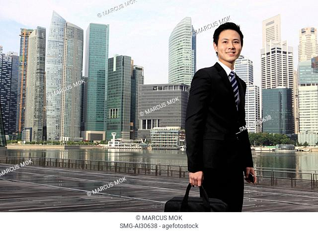 Young man wearing a business suit standing in front of buildings