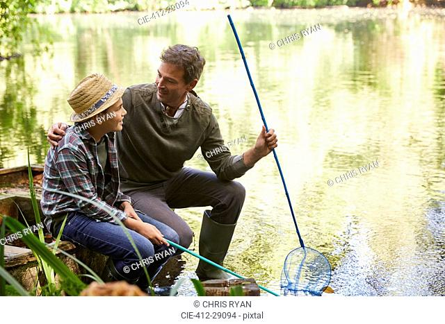 Father and son fishing with nets in pond